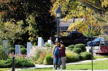 A Wilton woman fixes a scarecrow on a lamp post for the town's annual scarecrow fest.