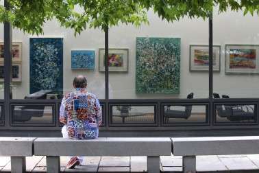 Norwalk artist Mark Schiff gazes upon his artwork hanging on the walls of Wilton Library.