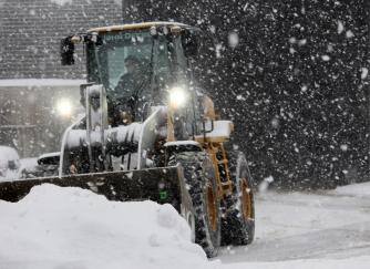 Pat Cavalier, a 28-year snowplow veteran, clears parking lots during a winter storm in Wilton.