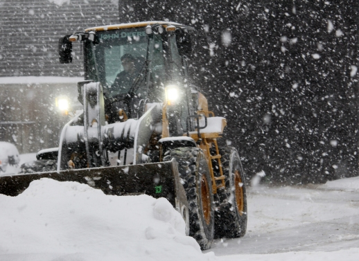 Pat Cavalier, a 28-year snowplow veteran, clears parking lots during a winter storm in Wilton.