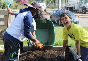 Wyatt Jones helps aerate the garden beds in front of Trackside Teen Center for Wilton's Green Teens program on Wednesday.