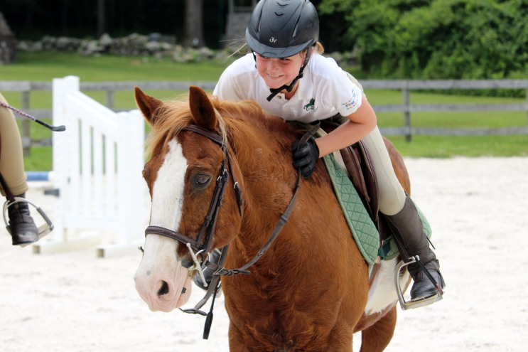 Hope Schlageter pets her horse, JP, after a successful practice at the Wilton Pony Club on the last day of summer camp on June 30, 2017.