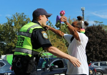Zeronia Gordon, of Norwalk, hugs Wilton Police Officer Brandon Harris after he gave her a rose as a random act of kindness on Friday, Sept. 22, 2017, in the Town Center.