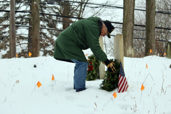 Navy veteran Ron Egut, of Norwalk, lays a wreath on the headstone of soldier buried at the cemetery near Comstock Lane and Signal Hill Road on Saturday, Dec. 17.